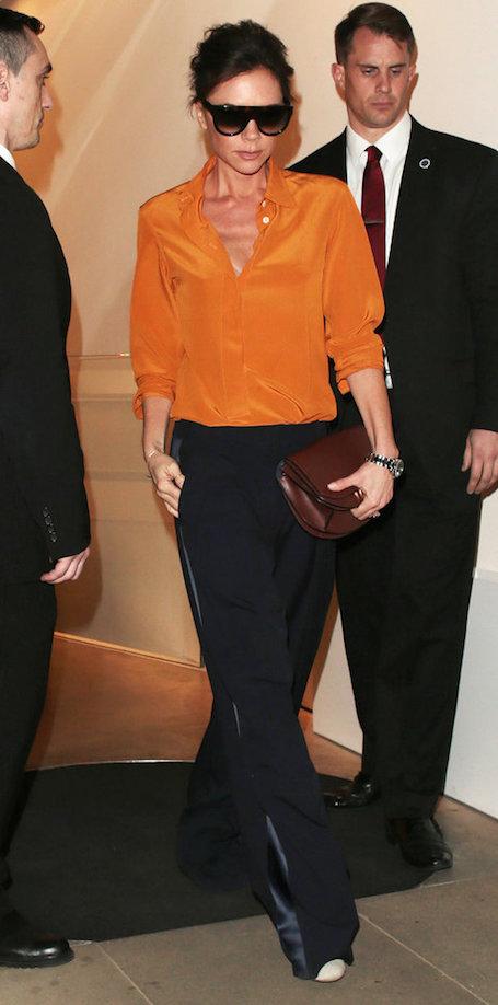 Апельсиновый топ и черные брюки - модный образ от Виктории Бекхэм. Фото